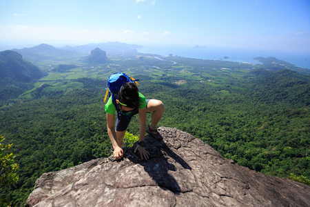 quirky: successful woman backpacker climbing up on seaside mountain rock Stock Photo