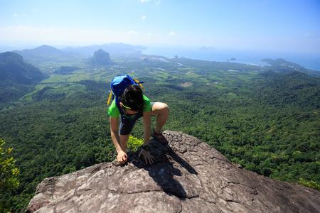 wanderlust: successful woman backpacker climbing up on seaside mountain rock Stock Photo