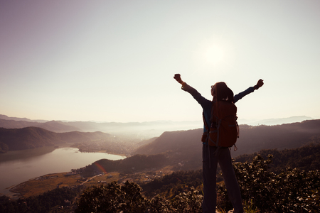 Successful woman backpacker on beautiful mountain top Stock Photo