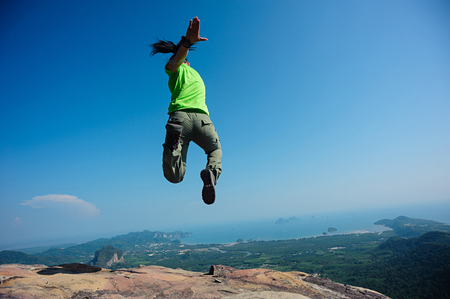 quirky: freedom woman jumping on rocky mountain top