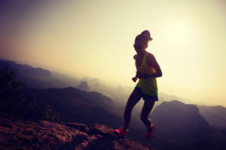 young woman running up on mountain top Stock Photo