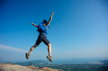 edges: cheering woman hiker jumping on rocky mountain top Stock Photo