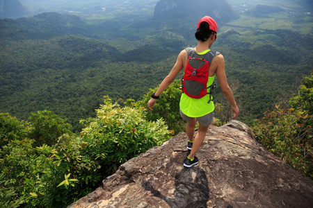 survive: Young fitness woman trail runner running at mountain top