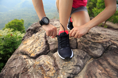 survive: Young fitness woman trail runner tying shoelace at mountain top