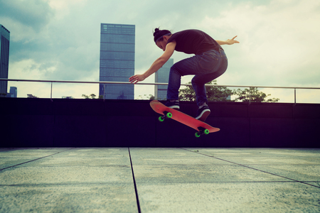 young woman skateboarder skateboarding at city