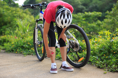 applied: Woman spraying mosquito repellent on skin before cycling in nature Stock Photo