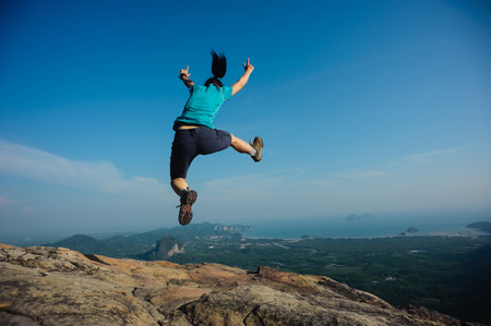 successful woman jumping on rocky mountain peak