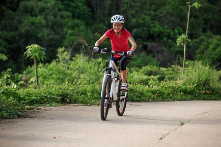 Vrouw fietser fietsen op zomer bos trail