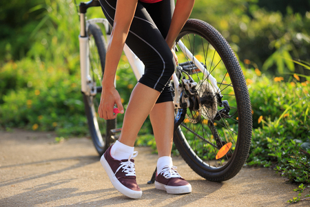 malaria: Woman spraying mosquito repellent on skin before cycling in nature Stock Photo