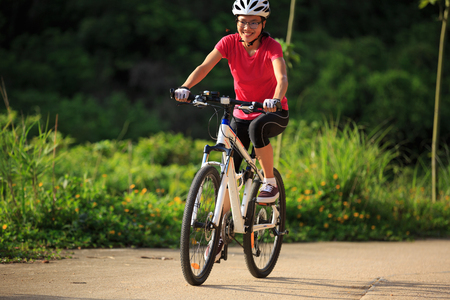 extreme weather: woman cyclist cycling on summer forest trail