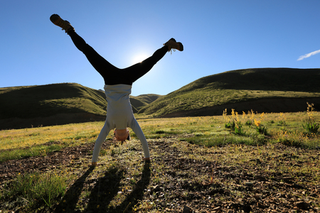 woman doing a handstand in a sunrise meadow Stock Photo