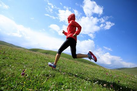Corredor de mujer joven fitness corriendo en pastizales de montaña Foto de archivo - 83312091