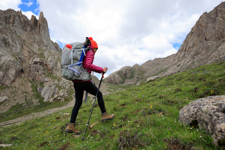 young woman with backpack hiking in mountains