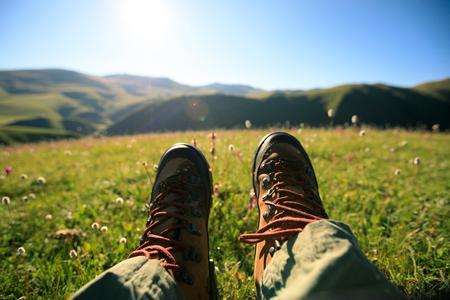 초원 산 꼭대기에서 등산객 다리 하이킹