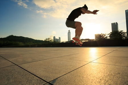 Woman practicing with skateboard at sunrise city Stock Photo