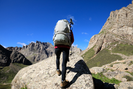 high sierra: successful woman with backpack hiking in mountains