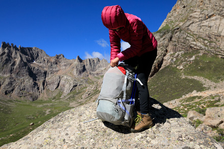 successful woman with backpack hiking in mountains