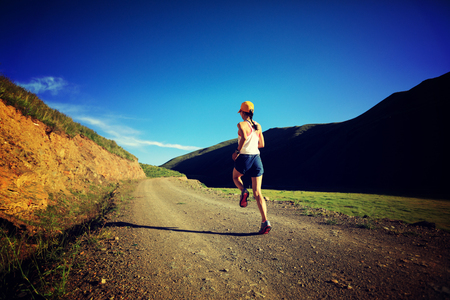 young fitness woman runner running on mountain trail photo