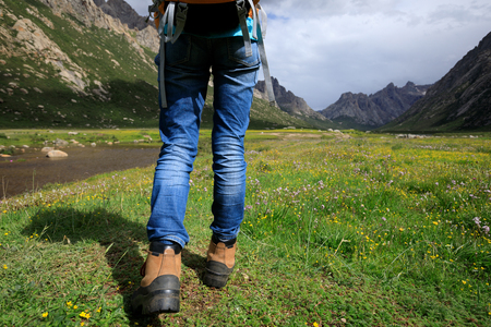 young backpacking woman hiking in mountains Stock Photo
