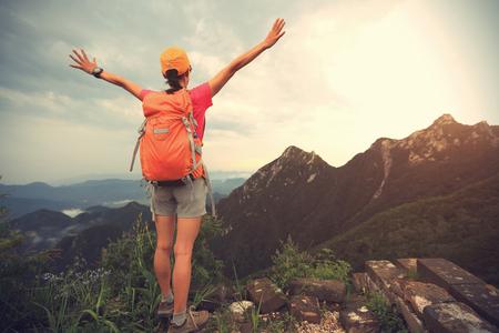 Femme réussie randonneuse bras ouverts sur le sommet de la montagne photo