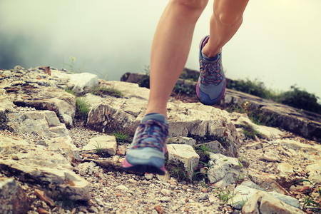 young woman trail runner legs running on great wall in the top of mountain photo