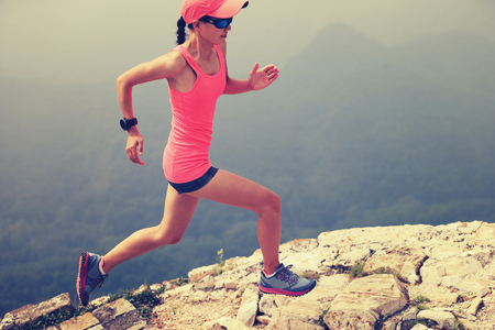 young woman trail runner running on great wall in the top of mountain photo