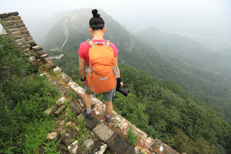 young woman photographer with camera on top of great wall photo