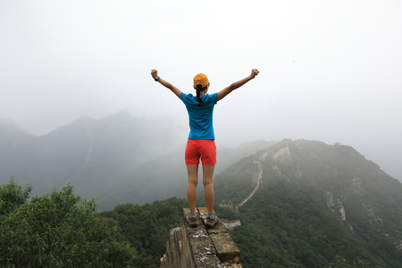 freedom woman hiker open arms to the great wall on the top of mountain photo