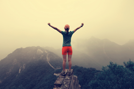 successful woman hiker open arms to the great wall on the top of mountain photo