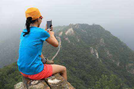 young woman hiker taking photo with smart phone on top of great wall Stock Photo