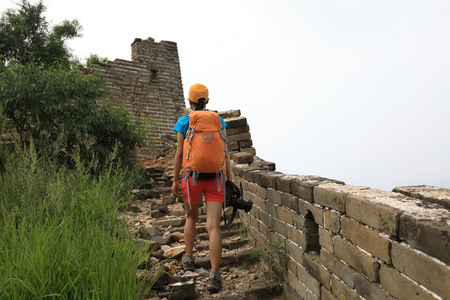 young woman hiker with camera on great wall photo