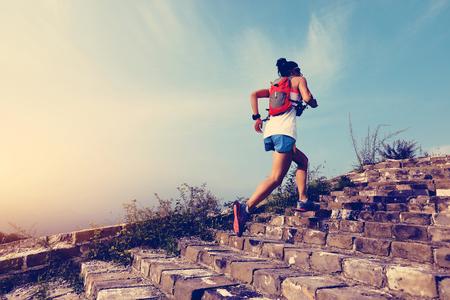 피트 니스 여자 흔적 러너 산 꼭대기에 큰 벽에 실행