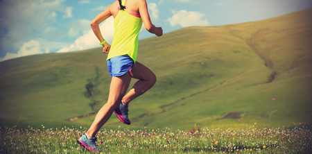 young fitness woman trail runner running on mountain grassland Stock Photo
