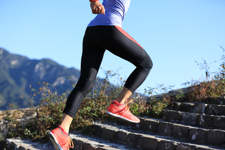 young fitness woman trail runner running on top of mountain Stock Photo