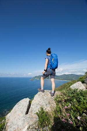 successful woman backpacker enjoy the view on seaside mountain top