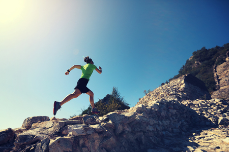 woman trail runner running at mountain top 写真素材