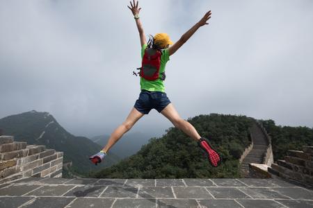 위대한 벽에 점프 성공적인 여자 등산객