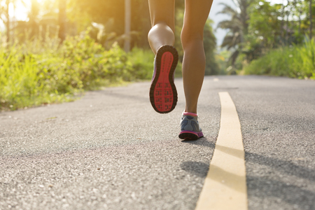 young fitness woman runner running on the forest trail Stock Photo