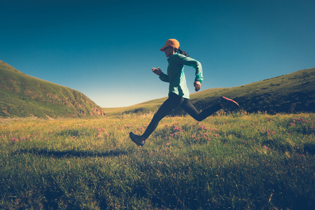 fitness woman trail runner running on grassland trail