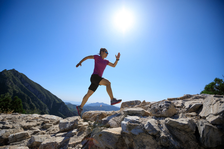 woman trail runner running at great wall on the top of mountain