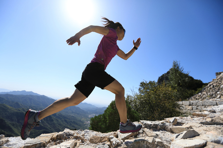 woman trail runner running at mountain top Stock Photo