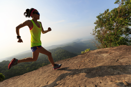 young woman trail runner running  up on mountain top