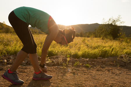 woman runner tying shoelace on forest trail