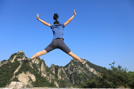 successful woman hiker jumping on mountain top