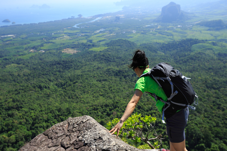 woman backpacker looking down on mountain peak cliff