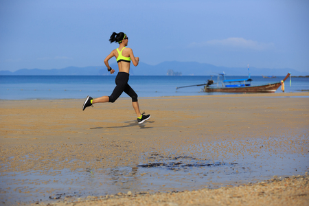 Young fitness woman running on sandy beach Stock Photo