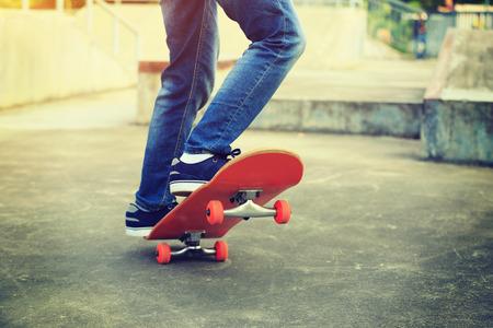 skate park: skateboarder legs skateboarding on skatepark ramp Stock Photo