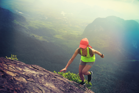Young fitness woman trail runner running up to  mountain top Stock Photo