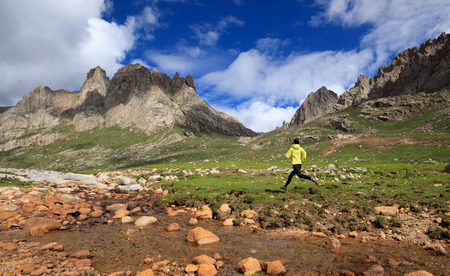 young woman trail runner running at high altitude mountains Stock Photo