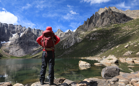 woman hiker with backpack hiking at high altitude mountains Stock Photo